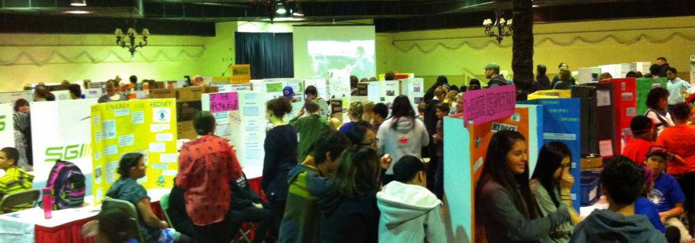 picture of a busy science fair with teens and adults