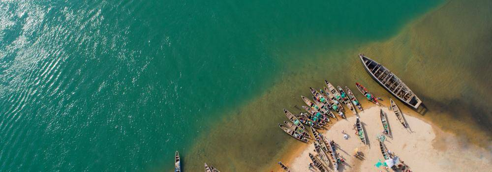 Aerial view of fishing boats parked on sand along a clear blue lake